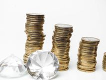 Monedas euro, diamantes que mienten en la tabla blanca foto de archivo