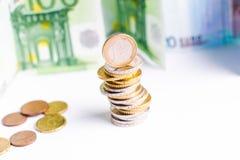 Monedas euro Dinero euro en un fondo blanco La estructura de monedas en un top es billete de banco del euroAnd en un fondo blanco Foto de archivo libre de regalías