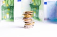 Monedas euro Dinero euro en un fondo blanco La estructura de monedas en un top es billete de banco del euroAnd en un fondo blanco Fotos de archivo libres de regalías