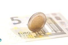 2 monedas euro en billetes de banco Foto de archivo libre de regalías