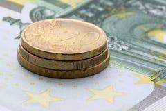 Monedas euro en cientos billetes de banco del euro Foto de archivo