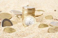 Monedas euro en la arena Fotografía de archivo