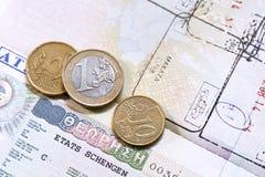 Monedas euro en pasaporte con la visa griega de la unión europea Fotografía de archivo