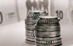 Monedas euro y billetes de banco y siluetas borrosos de la gente Foto de archivo libre de regalías