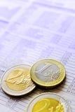 Monedas euro y noticias de Bursa en el periódico Fotos de archivo