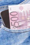 Monedas euro y teléfono móvil para pagar cashless en el bolsillo de vaqueros Finanzas y actividades bancarias imagenes de archivo