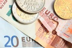 Monedas griegas en notas euro Imagen de archivo