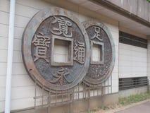 Monedas japonesas grandes en la pared fotografía de archivo
