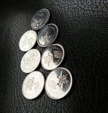Monedas malasias en el cuero negro Imagen de archivo libre de regalías