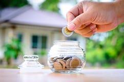 Monedas masculinas del dinero del ahorro de la mano con el hom Imágenes de archivo libres de regalías