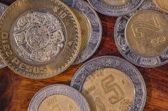 Monedas mexicanas de $5 y $10 Pesos en el medio de otras monedas en una tabla de madera imágenes de archivo libres de regalías