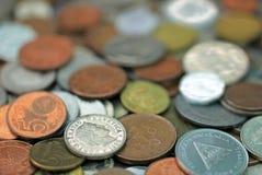 Monedas mezcladas de la moneda del mundo, franco suizo en foco imagen de archivo