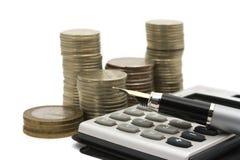 Monedas, pluma y calculadora Imagenes de archivo