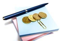 Monedas, pluma y papel Imagenes de archivo
