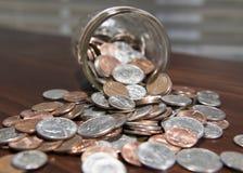 Monedas que caen del tarro 2 Imagen de archivo libre de regalías