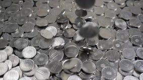 Monedas que caen en la cámara lenta metrajes