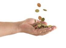 Monedas que caen en una mano Imágenes de archivo libres de regalías