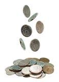 Monedas que caen en una pila en blanco Imágenes de archivo libres de regalías
