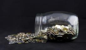 Monedas que desbordan un tarro Fotos de archivo
