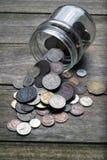 Monedas que desbordan un tarro imágenes de archivo libres de regalías