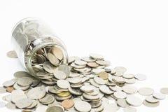 Monedas que desbordan un tarro del dinero Foto de archivo libre de regalías