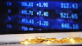 Monedas que desmenuzan de la cámara lenta del recurso de Bitcoin contra la pantalla