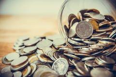 Monedas que se derraman fuera de una botella de cristal imágenes de archivo libres de regalías