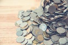 Monedas que se derraman fuera de una botella de cristal fotografía de archivo