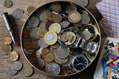 Monedas, relojes, naipes y una cáscara de la bala Imagen de archivo