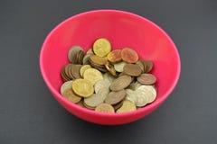 Monedas rusas comunes en taza rojo-rosada Monedas rusas recogidas en taza plástica roja Fotografía de archivo libre de regalías