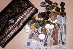 Monedas rusas del dinero y billetes de papel de diversas denominaciones y un monedero en la tabla foto de archivo