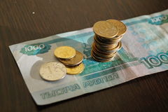 Monedas rusas en un billete de banco en 1000 rublos Imágenes de archivo libres de regalías