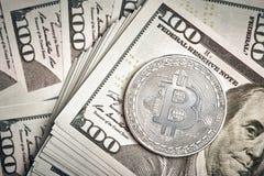 Monedas simbólicas del bitcoin en los billetes de banco de cientos dólares Efectivo del bitcoin del intercambio para un dólar Fotografía de archivo