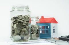 Monedas, tarro y casa en el fondo Foto de archivo
