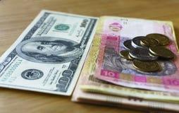 Monedas ucranianas del metal de 1, 2 hryvnias apiladas contra 100 dólares americanos, de la reducción de los hryvnias y del dólar imágenes de archivo libres de regalías