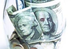Monedas y billete de banco en un tarro de cristal en el fondo blanco Imagen de archivo libre de regalías