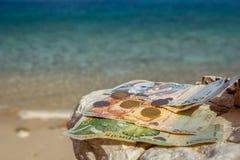 Monedas y billetes de banco albaneses en la playa foto de archivo