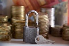 Monedas y billetes de banco apilados detrás de un candado con una llave imágenes de archivo libres de regalías