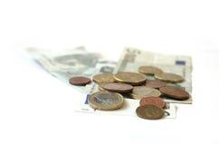 Monedas y billetes de banco de los euros del efectivo en blanco Foto de archivo libre de regalías