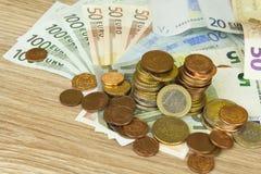Monedas y billetes de banco euro en la tabla Vista detallada de la moneda de curso legal de la unión europea, UE Imagen de archivo
