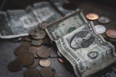 Monedas y billetes de dólar dispersados en la tabla concreta foto de archivo libre de regalías