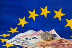 Monedas y billetes euro delante de la bandera de la UE Fotografía de archivo libre de regalías