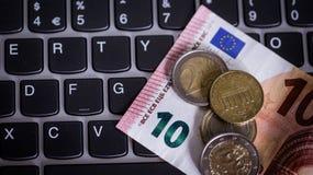 Monedas y billetes euro sobre el laptop& x27; teclado de s fotos de archivo libres de regalías