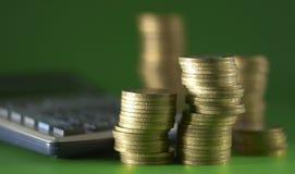 Monedas y calculadora Fotos de archivo