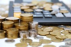 Monedas y calculadora Fotografía de archivo libre de regalías