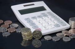 Monedas y calculadora Imagen de archivo