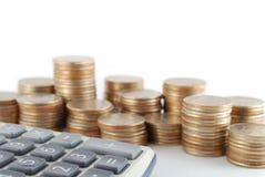 Monedas y calculadora Foto de archivo libre de regalías