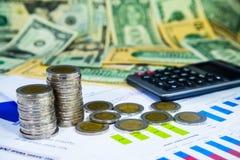 Monedas y calculadora, en diagrama financiero Fotos de archivo libres de regalías