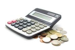 Monedas y calculadora en el fondo blanco Imagen de archivo libre de regalías