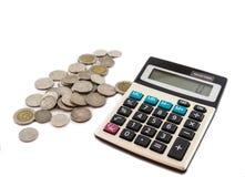 Monedas y calculadora en el fondo blanco Fotos de archivo